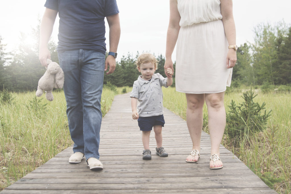 family of 3 walking on a boardwalk