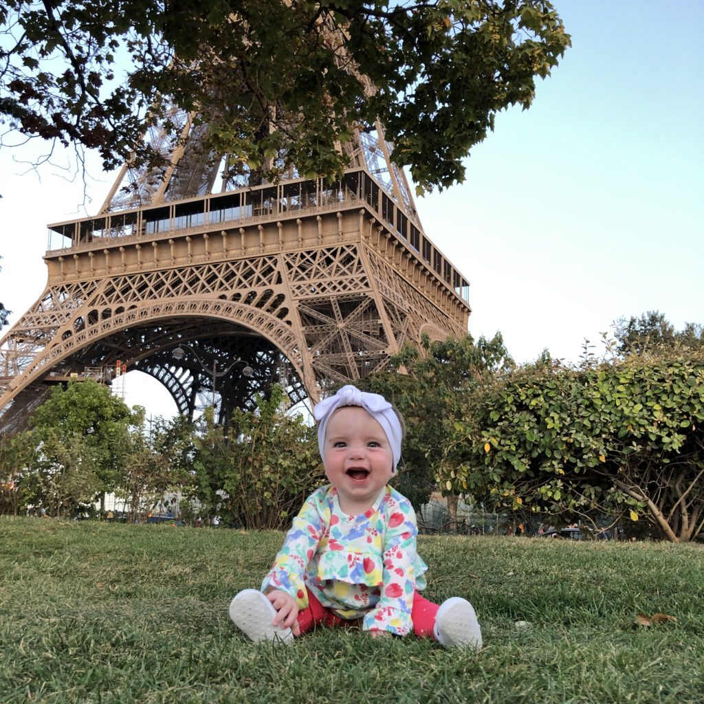 Baby witting in front of the Eiffel Tower